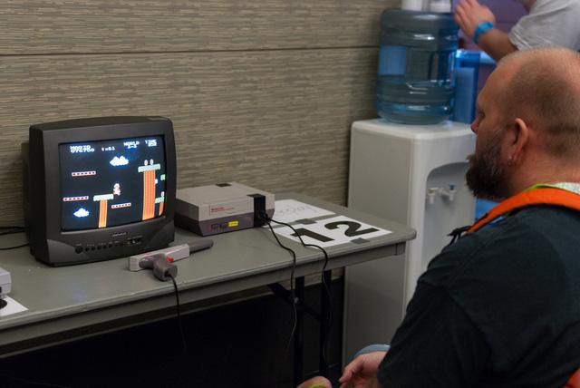 Giống như anh chàng trong hình này nhưng anh ta sử dụng máy NES ban đầu chứ không phải máy NES đầu đọc phía trên.