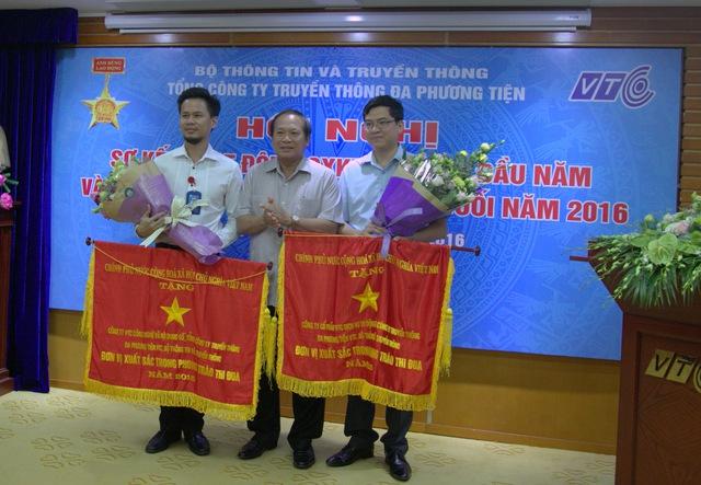 Ông Nguyễn Thanh Hưng (bên trái) nhận hoa và cờ từ Bộ trưởng Bộ Thông tin và Truyền thông