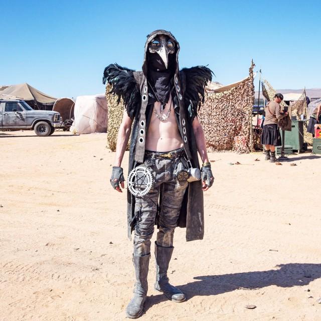 Một người tham dự trong trang phục dựa theo loài quạ trước trại của bộ lạc mình